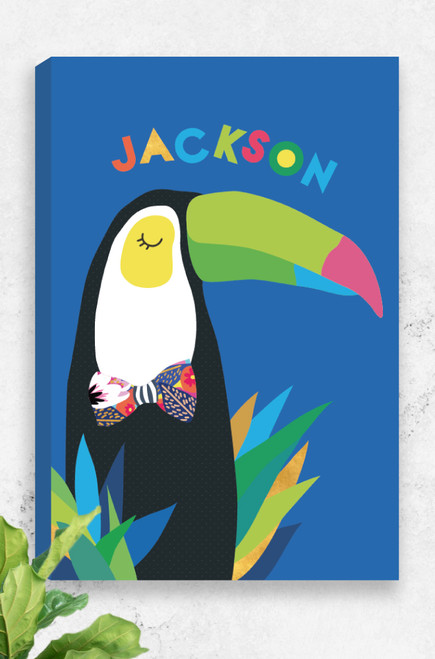 A bright and colourful, ready to hang canvas personalised with the name of a child at the top. Featuring a vibrant and happy toucan, a patterned bow-tie and bright foliage at the bottom. Set on a vibrant cobalt background, this canvas is a unique gift idea for a special little boy.