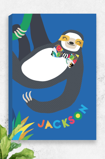 A ready to hang canvas with a happy go lucky sloth hanging from a green vine from the top of the artwork. He has gold patches behind his friendly eyes and a vibrant bow-tie around his neck. Personalised underneath in a playful font with the name of a child. A perfect gift idea for a new baby boy.