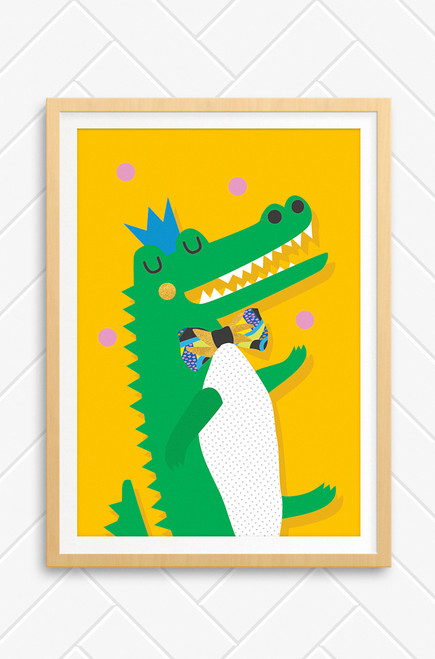 A bright orange wall art print featuring a green crocodile dancing and juggling pink balls over it's head. The crocodile has a big smile revealing it's white teeth. It wears a patterned bow tie and blue crown on its head. Framed in an oak frame, also available unframed. Designed by Luca Rose Designs in rural NSW Australia.