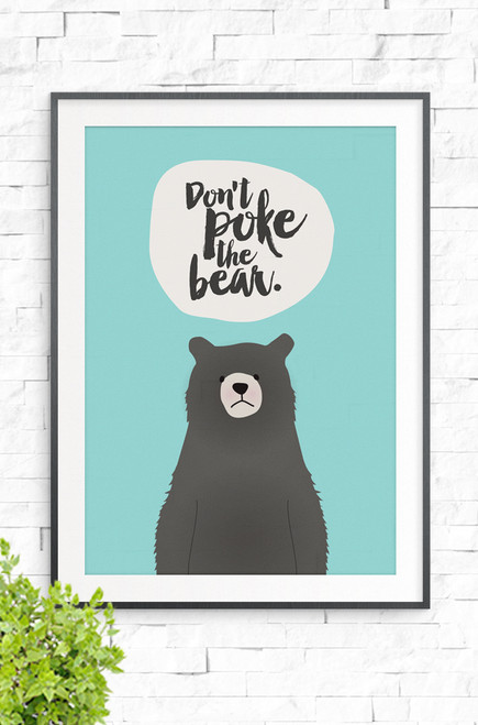 A wall art print with a black frame on a white brick wall. The illustration features a brown bear with a grumpy facial expression. Above it is a beige colored bubble with the words 'Don't Poke The Bear' written in a brush style font.