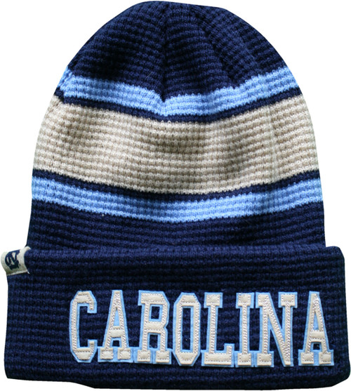 Cable knit toboggan mostly navy with broad crme stripe offset with Carolina Blue lines.  The ltters CAROLINA are sewn on the cuff.