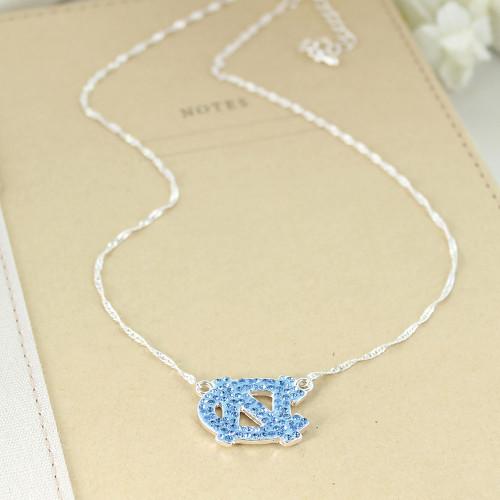 Carolina Blue rhinestones in shape of interlocking NC on silver necklace