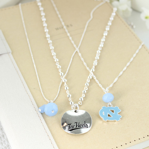 3 silver necklaces 1 Carolina Blue beads - one with interlocking NC - one with silver pendant with Tar Heels etched in it.
