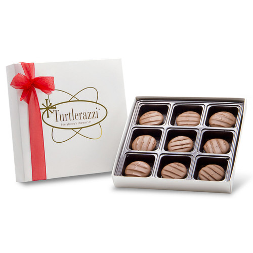 Turtlerazzi - 9 pieces of milk chocolate pecan clusters in a white gift box with a red ribbon