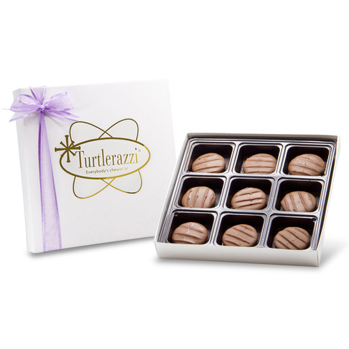 Turtlerazzi - 9 pieces of milk chocolate pecan clusters in a white gift box with a purple ribbon