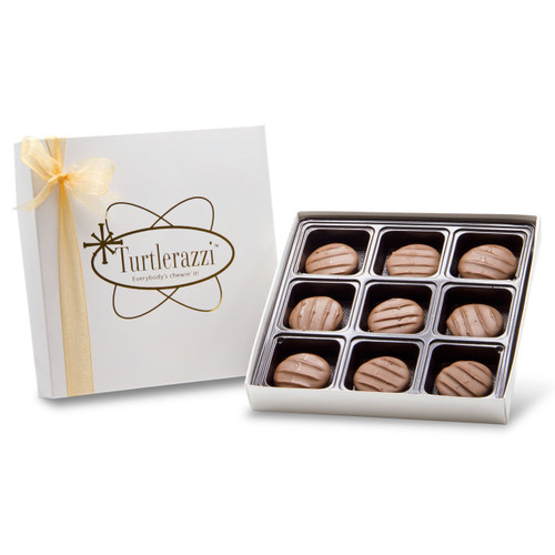 Turtlerazzi - 9 pieces of milk chocolate pecan clusters in a white gift box with a gold ribbon