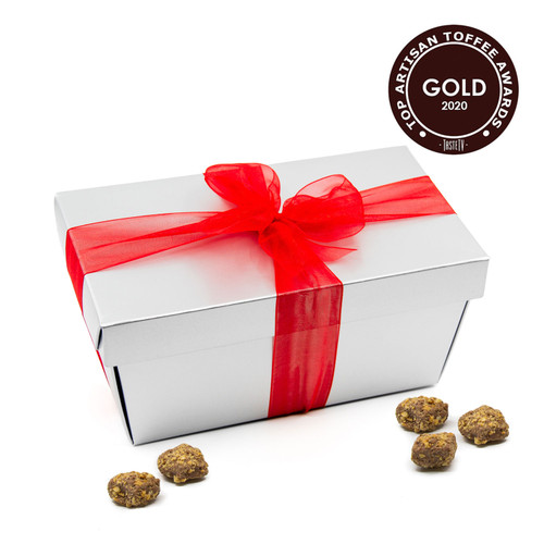 Toffarazzi Toffee bite size pieces in a silver gift box with a red ribbon.