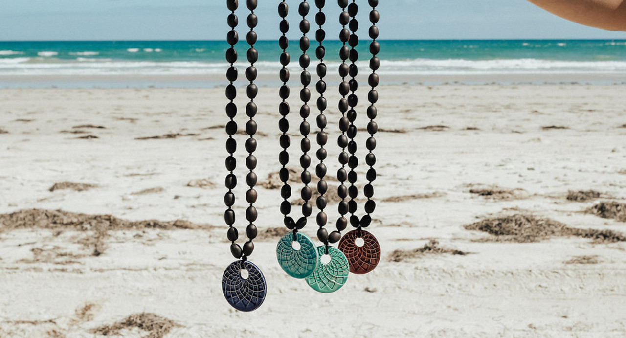 Beach background with 4 different pendant necklaces