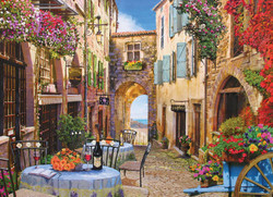 A old-style French village with outdoor cafe, bottle of red wine, and nice view of the ocean makes for a delightful puzzling experience from Cobble Hill Puzzles.