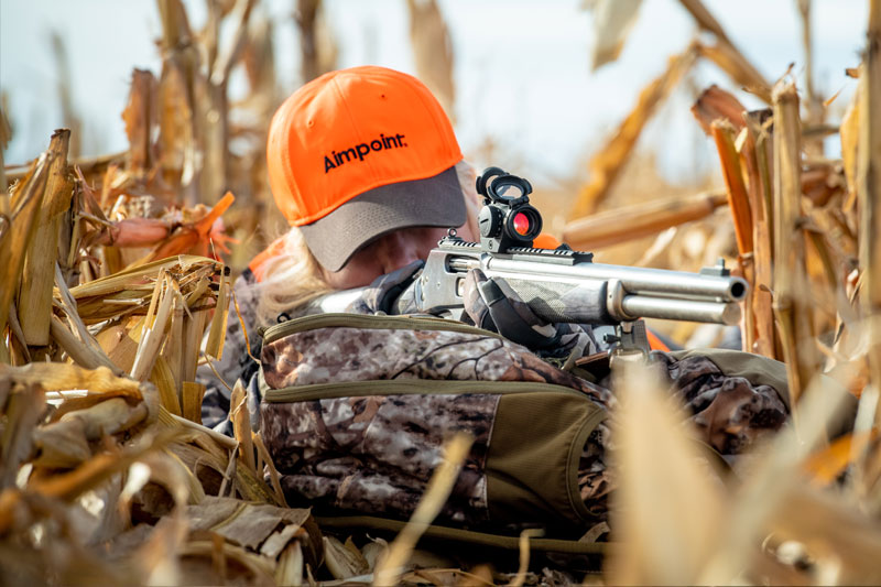 Hunter wearing Aimpoint branded orange hat
