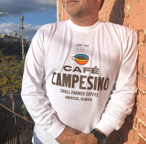 White long-sleeve tshirt made in the USA and bearing the Cafe Campesino logo on the front.