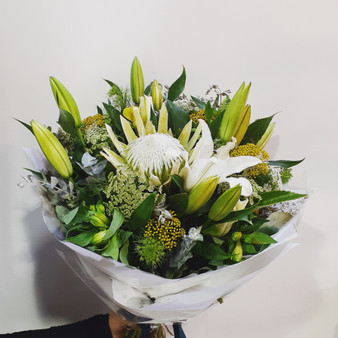 Mixture of seasonal flowers in whites and greens.