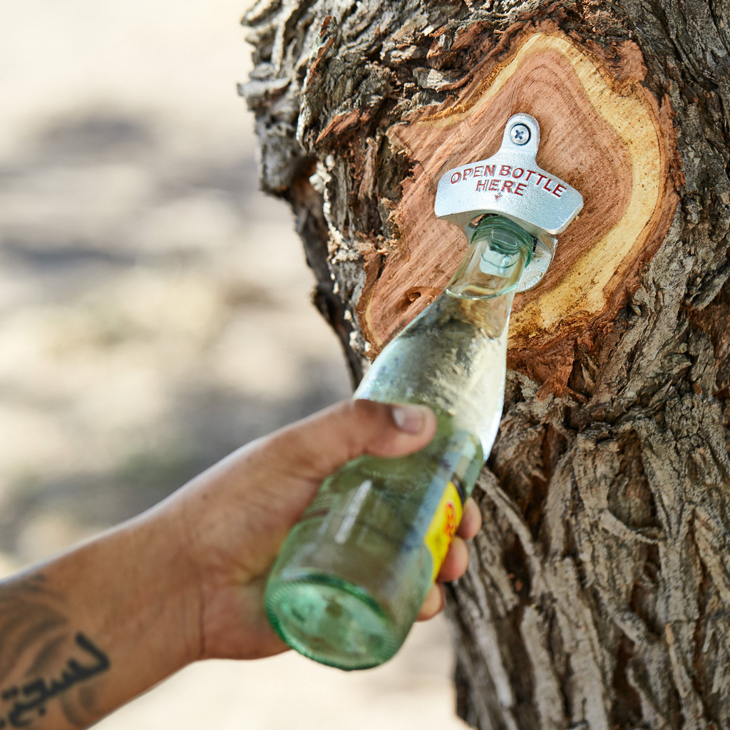 A Texan with good taste using Goode Co's Starr Bottle Opener to open a Topo Chico bottle.