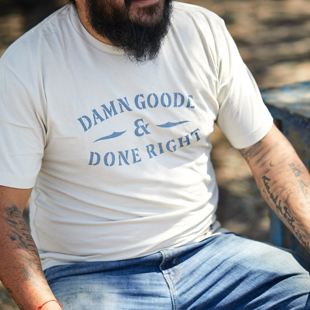 """Proud Texan wearing Goode Co's white cotton t-shirt that says """"Damn Goode & Done Right"""" in blue font."""