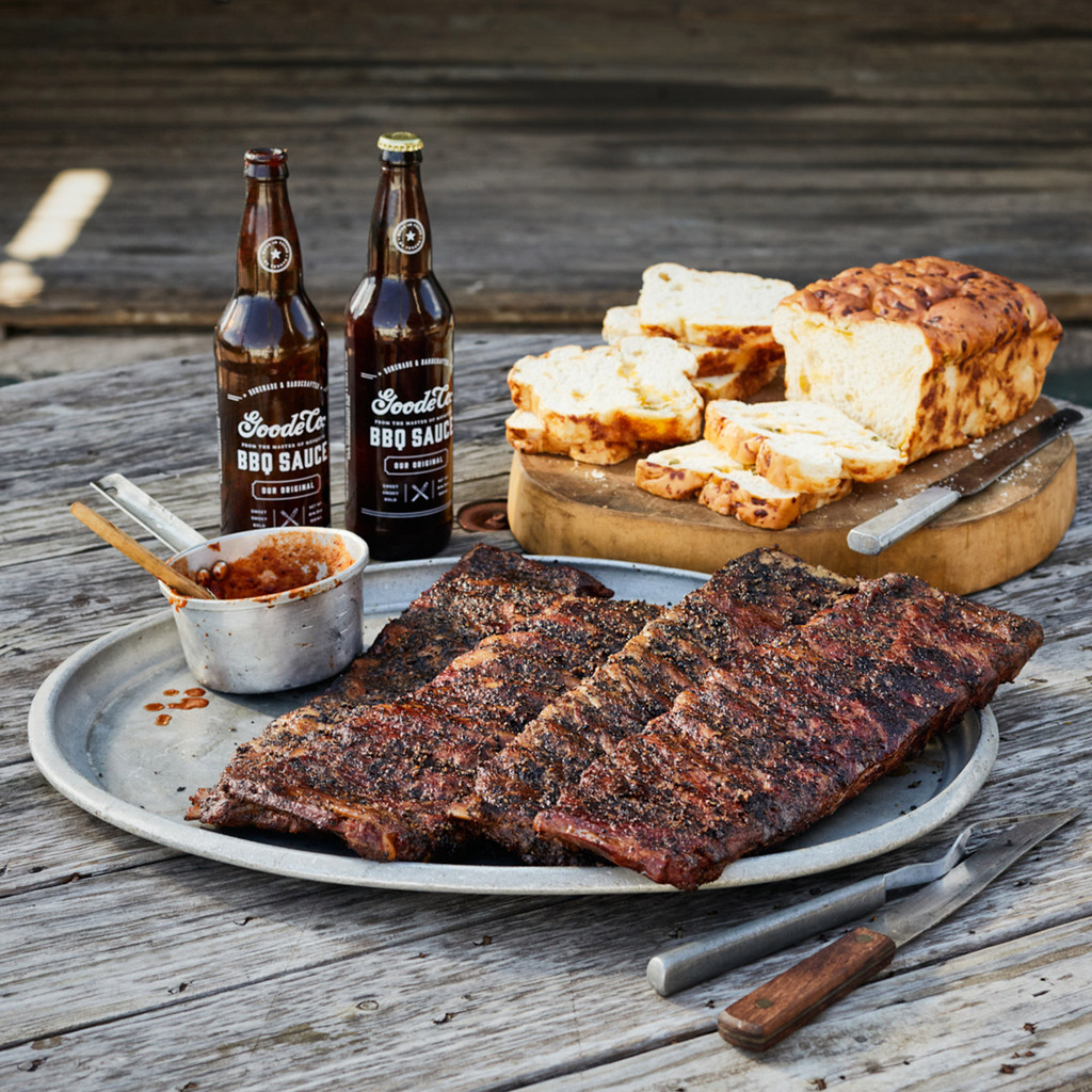 Goode Co's Texas Sized Smoked BBQ Ribs meal bundle, consisting of 4 slabs of pork ribs, 2 24.5-ounce bottles of Goode's BBQ Sauce, and 2 loaves of jalapeño cheese bread.