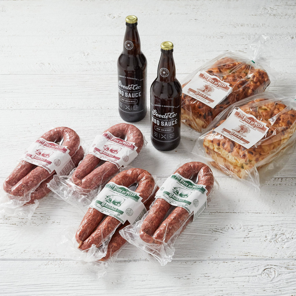 Shipping packaging for Texas Sized Sausage Sampler bundle with 4 vacuum-sealed links of Czech sausage, 4 links of Jalapeño Pork sausage, 2 24.5-ounce bottles of Goode's BBQ Sauce, and 2 loaves of jalapeño cheese bread.
