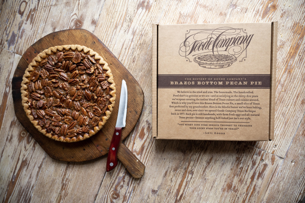 Brazos Bottom Pecan Pie with a knife next to it. To the right is a cardboard box with the Goode Company logo and a note about the pecan pie.