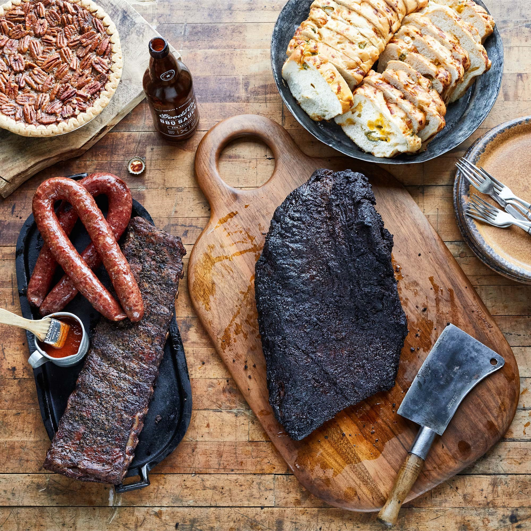 Goode Co's The Independence meal bundle, consisting of whole smoked brisket, rack of pork ribs, link of Czech sausage, link of jalapeño pork sausage, bottle Goode's Original BBQ sauce, and 2 loaves of jalapeño cheese bread.
