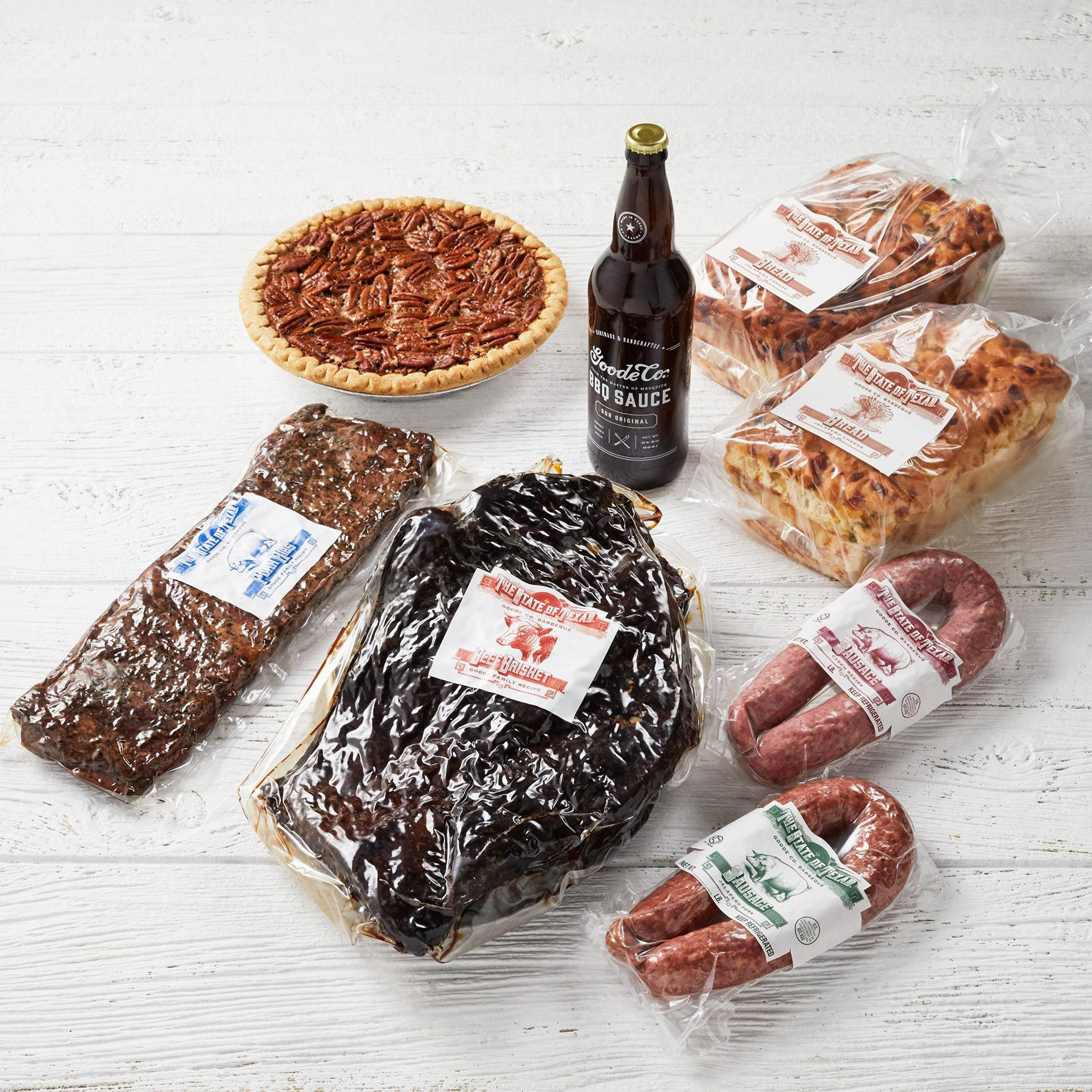 Shipping packaging for Goode Co's The Independence meal bundle. Vacuum-sealed smoked brisket, pork ribs, link of Czech sausage, and link of jalapeño pork sausage. Glass bottle of Goode's Original BBQ sauce, and 2 loaves of jalapeño cheese bread.
