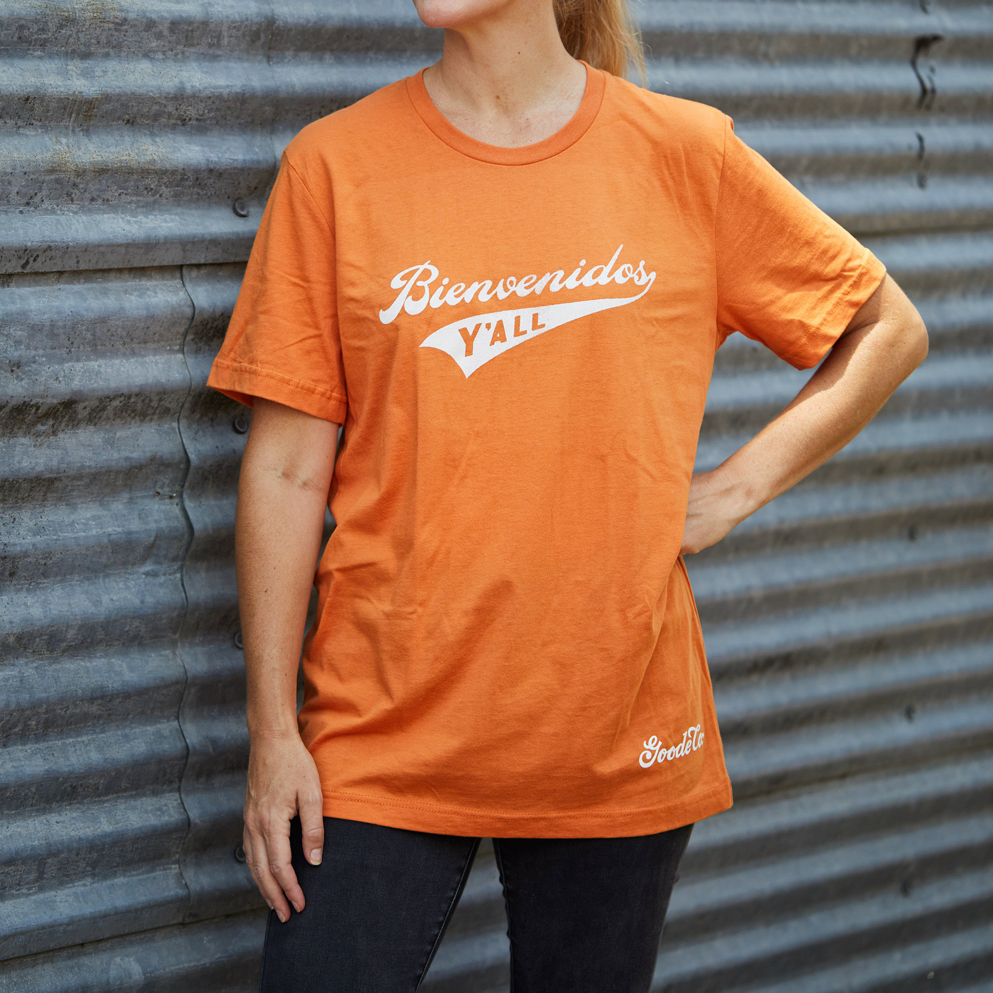 "Proud Texan wearing Goode Co's orange cotton t-shirt that says ""Bienvenidos Y'all"" in white font."