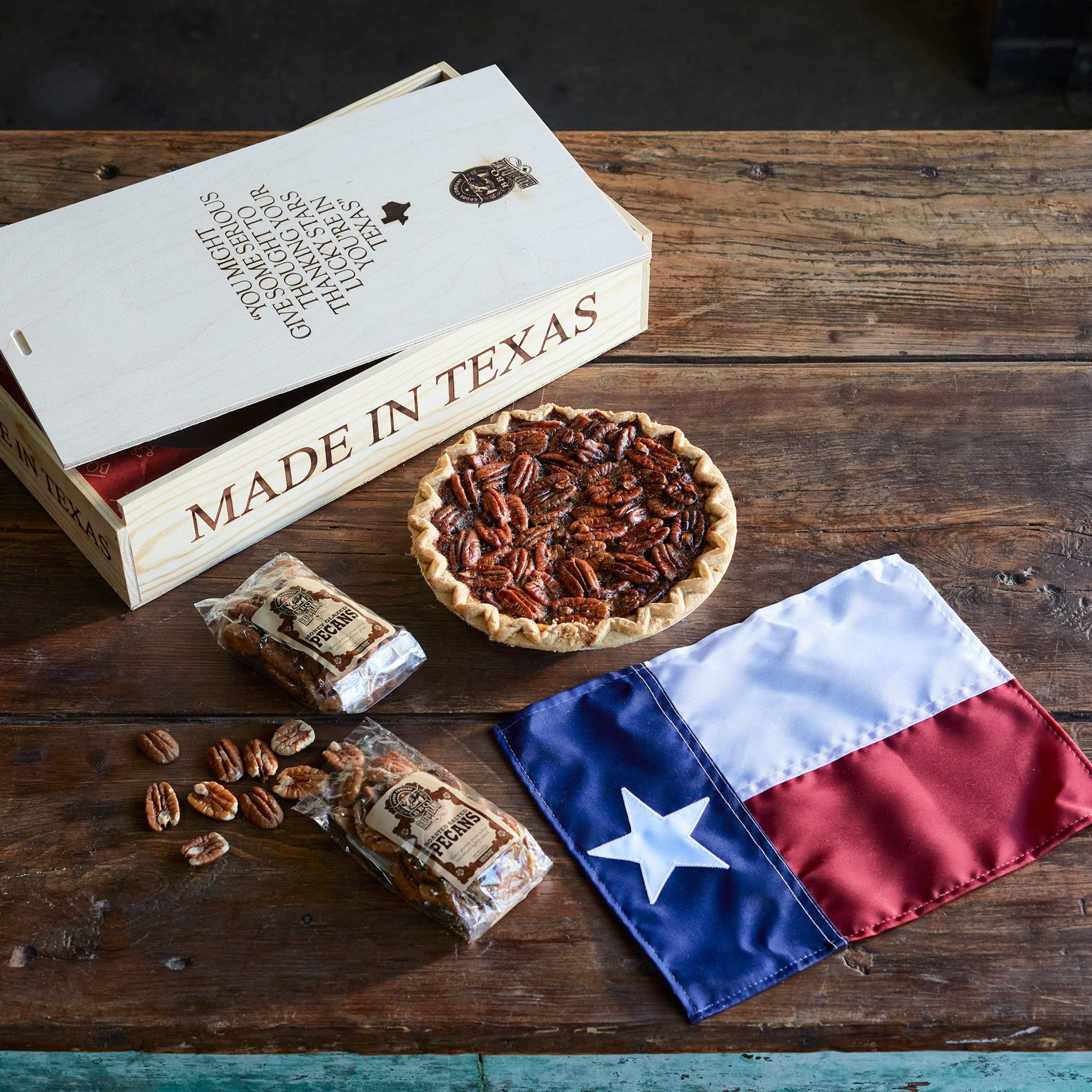 Goode Co's Pure Texas fire-branded wooden gift box, consisting of a personal-sized Brazos Bottom Pecan Pie, bag of Honey-Glazed Pecans, bag of Roasted Salted Pecans, and a mini Texas state flag.