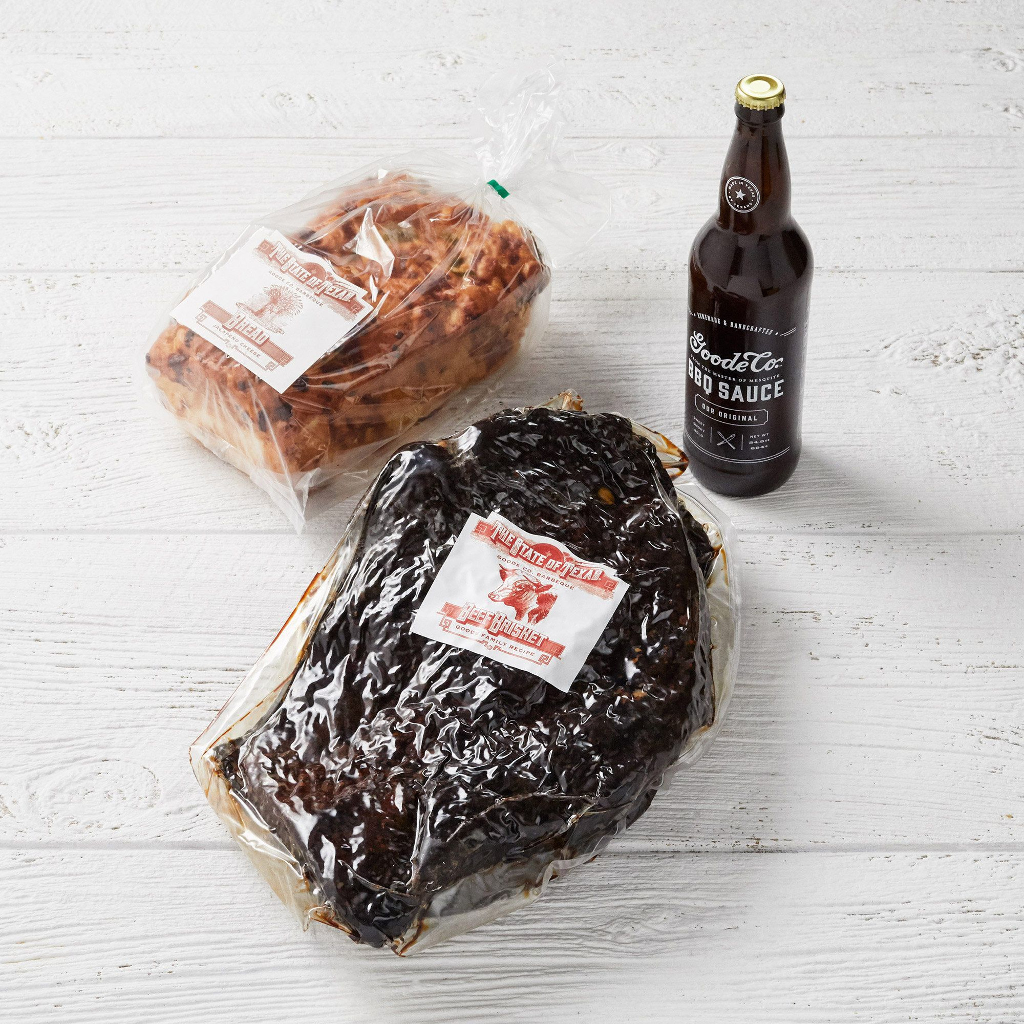 Vacuum-sealed packaging for Goode Co's Classic Mesquite Smoked Brisket with a glass bottle of BBQ sauce, and a loaf of jalapeño cheese bread.