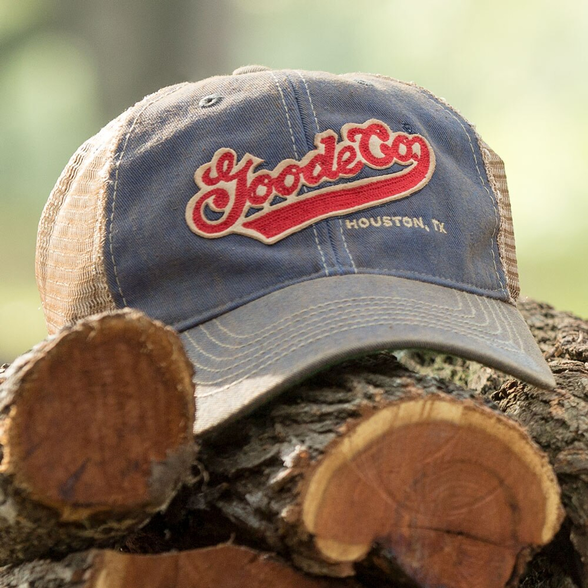 Goode Co's vintage-looking blue trucker hat resting on Texas mesquite wood.