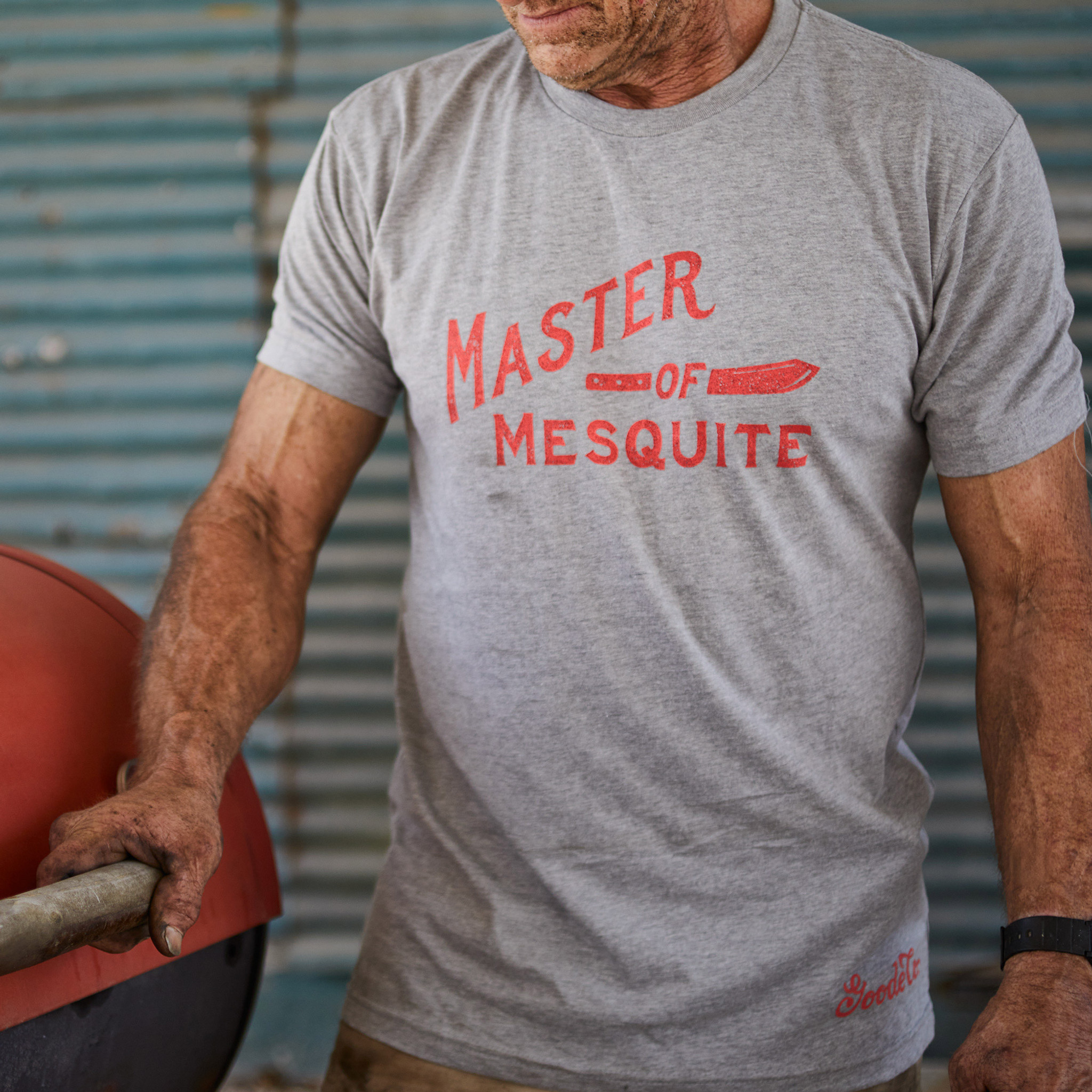 """Proud Texan wearing Goode Co's light grey cotton t-shirt that says """"Master of Mesquite"""" in red font."""