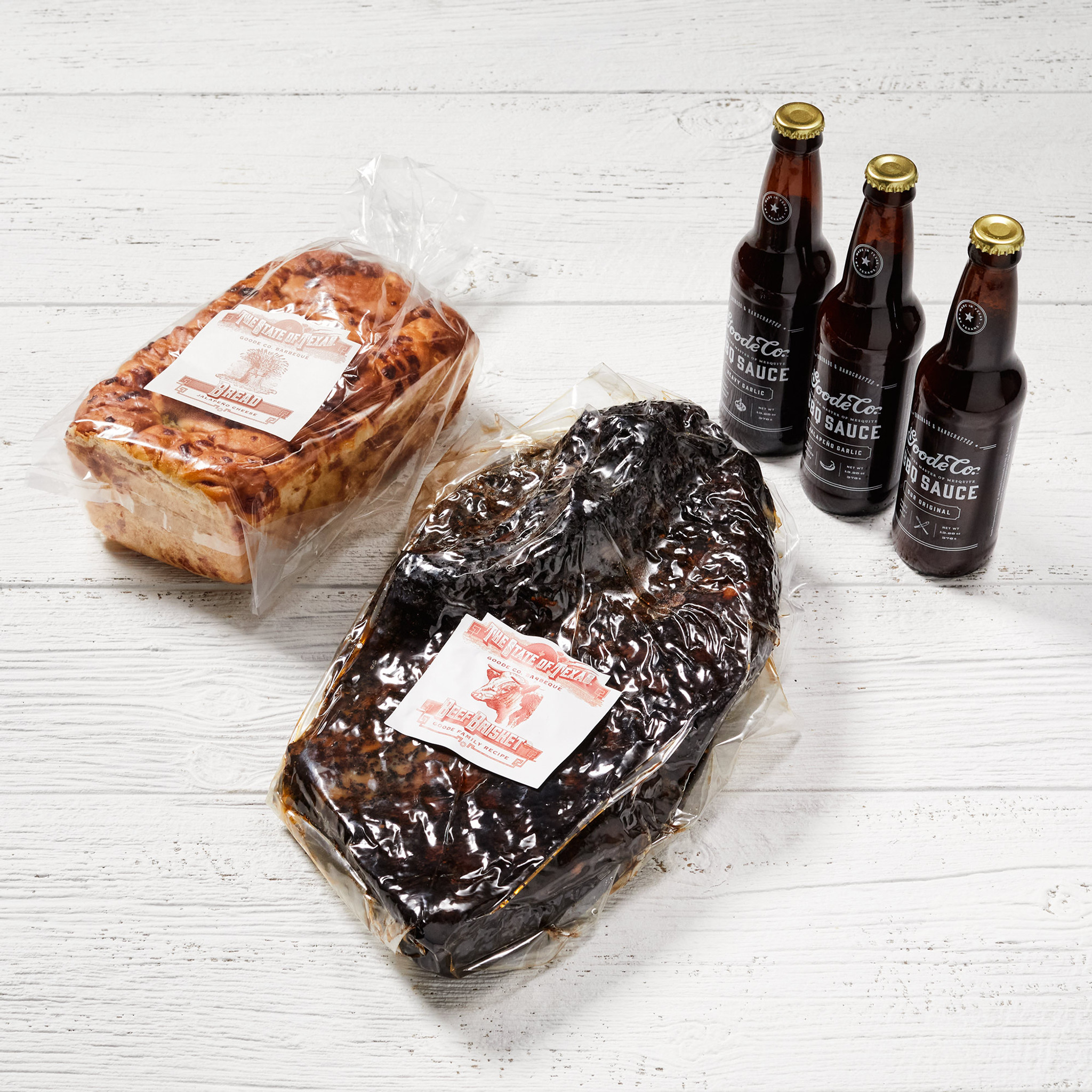 Shipping packaging for Goode Co's Brisket & BBQ Sauce Sampler bundle, delivered in vacuum-sealed smoked brisket with 3 glass bottles of Goode's Original BBQ sauce, and 1 loaf of jalapeño cheese bread.