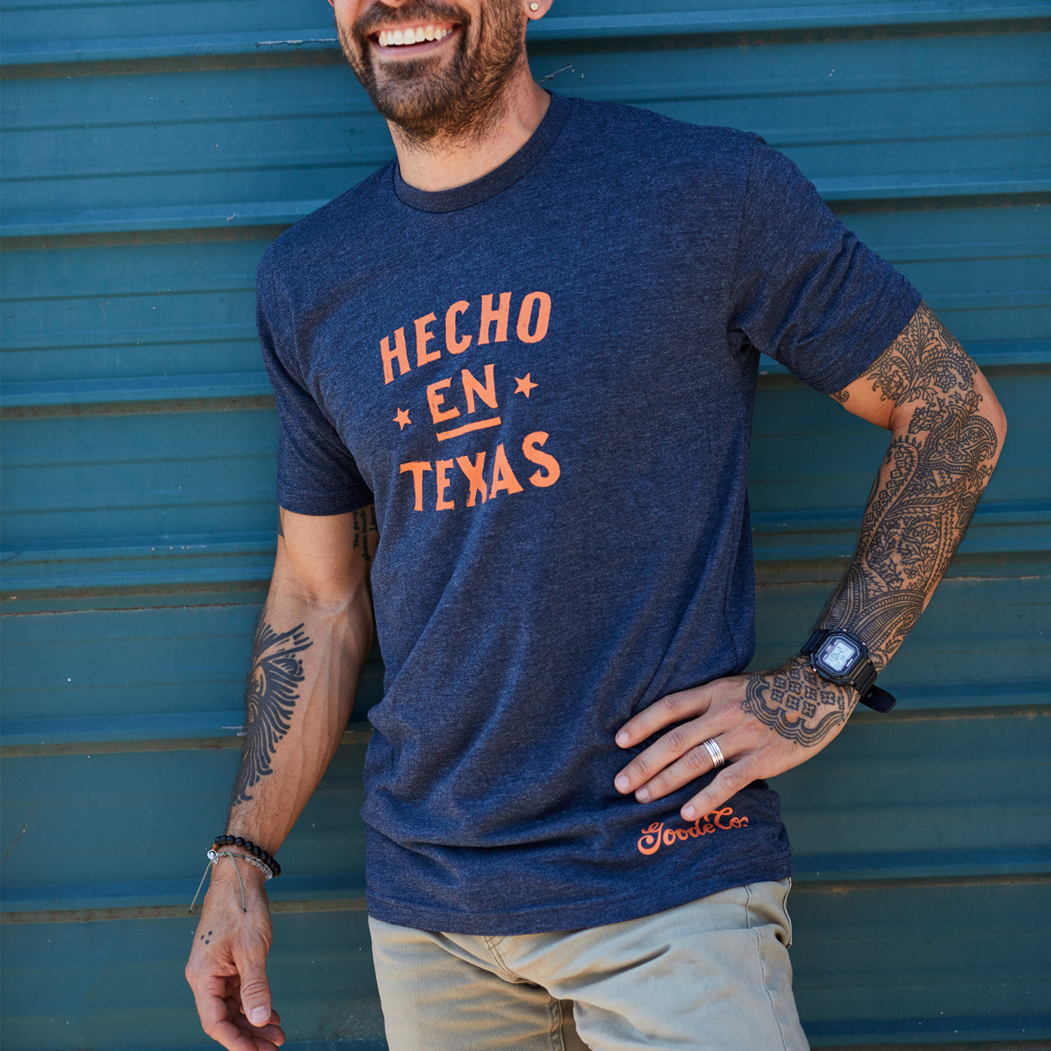 "Proud Texan wearing Goode Co's dark blue cotton t-shirt that says ""Hecho en Tejas"" in orange font."