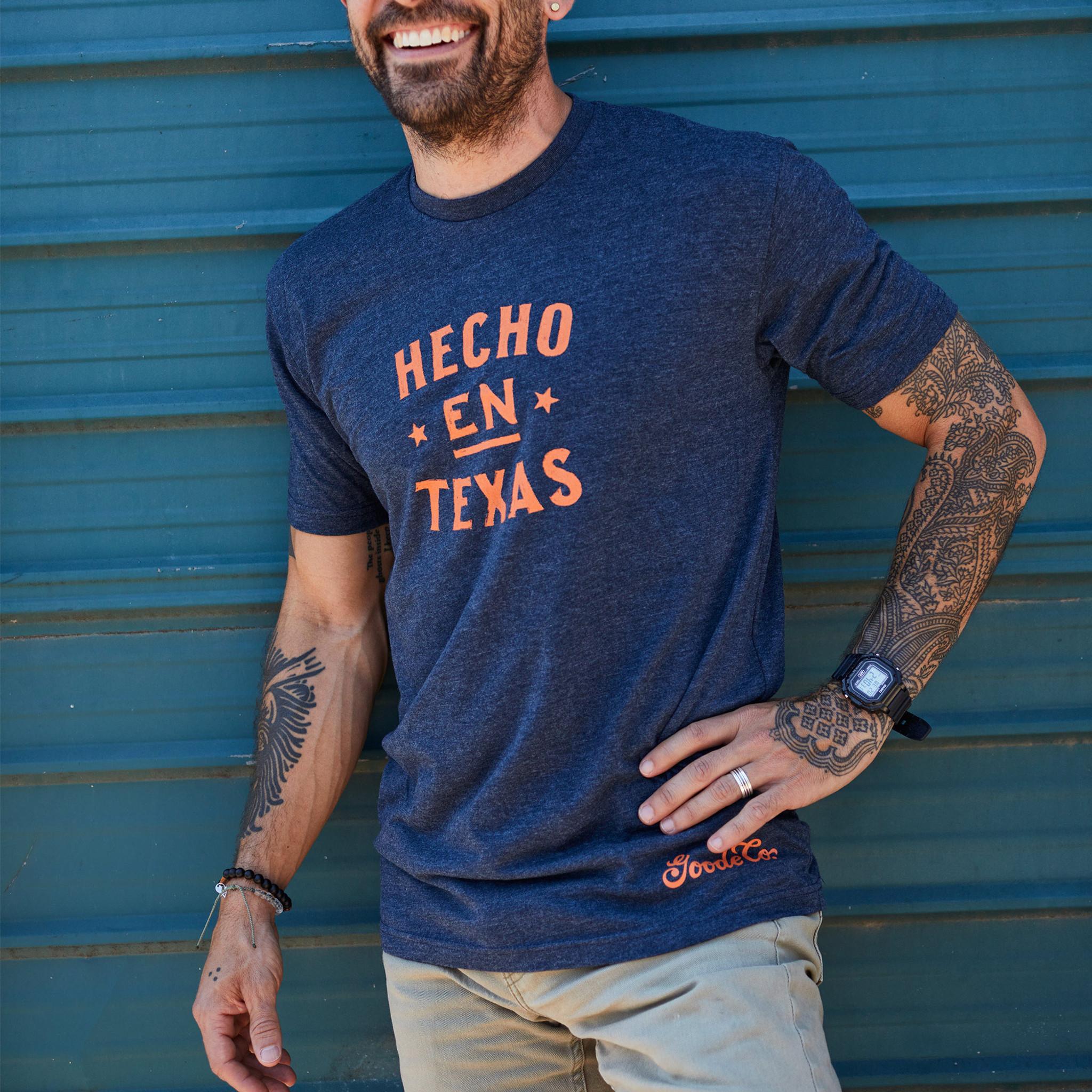 "Proud Texan wearing Goode Co's dark blue cotton t-shirt that says ""Hecho en Texas"" in orange font."
