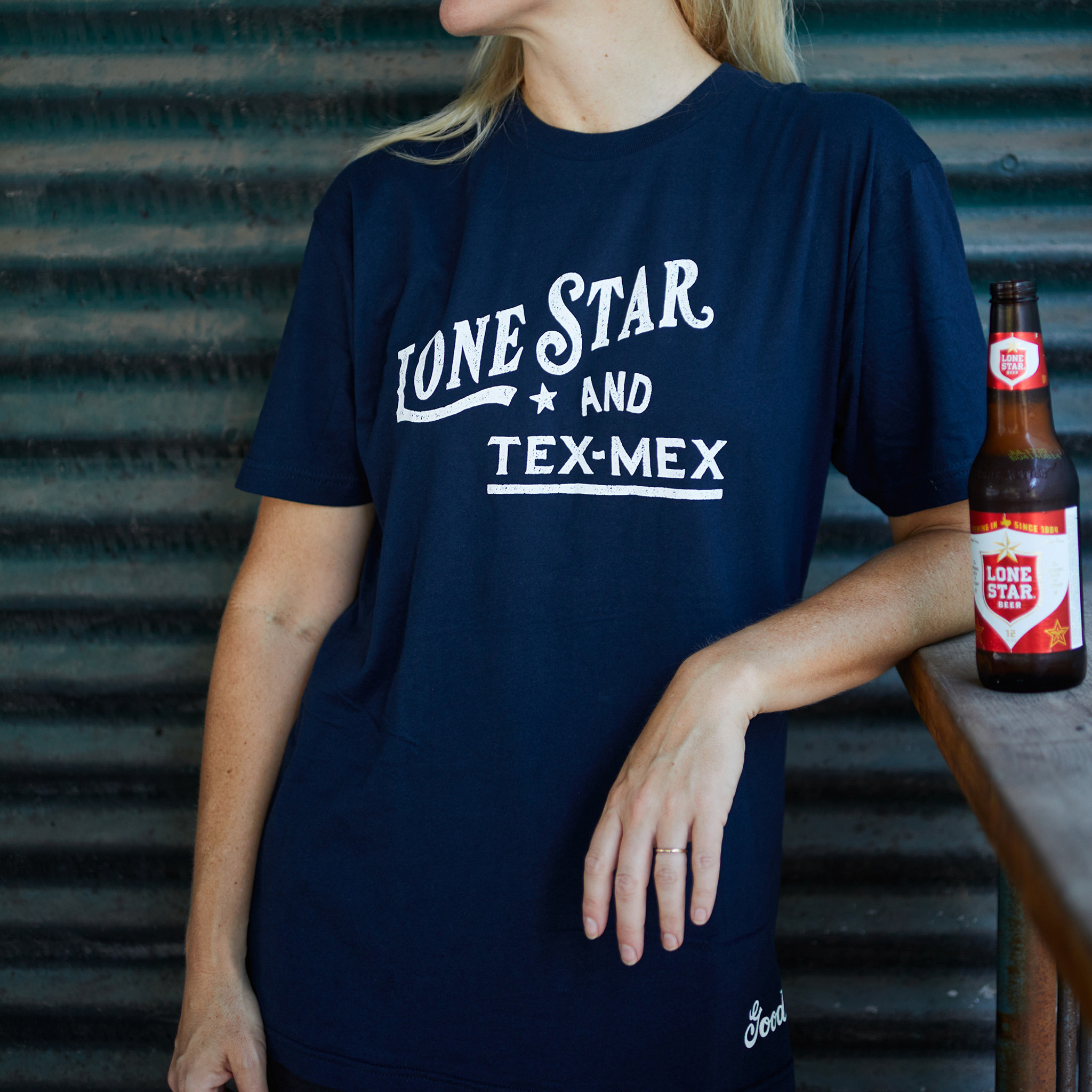 "Proud Texan wearing Goode Co's black cotton t-shirt that says ""Lone Star & Tex-Mex"" in white font."