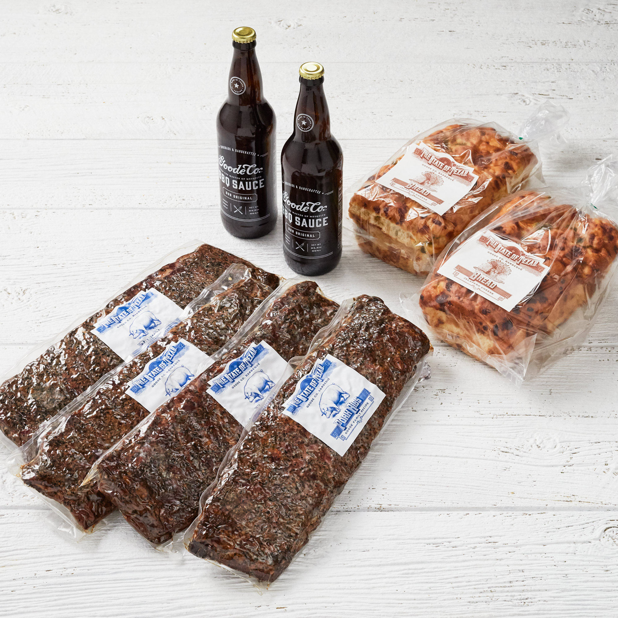 Shipping packaging for Texas Sized Smoked BBQ Ribs sampler bundle with 4 vacuum-sealed slabs of pork ribs, 2 24.5-ounce long-necked bottles of Goode's BBQ Sauce, and 2 loaves of jalapeño cheese bread.
