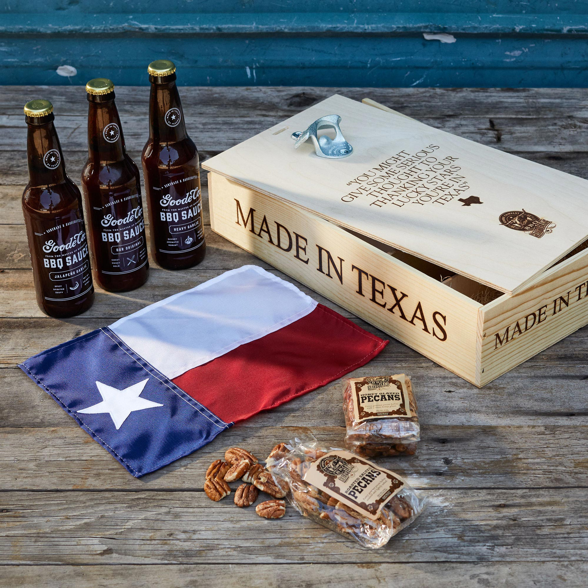 Goode Co's Uncle Joe's Secret Gift Box, consisting of 1 bottle each of Goode's Original BBQ, Heavy Garlic, & Jalapeño Garlic Sauces, 1 package each of Roasted Salted & Honey Glazed Pecans, and 1 miniature Texas state flag.