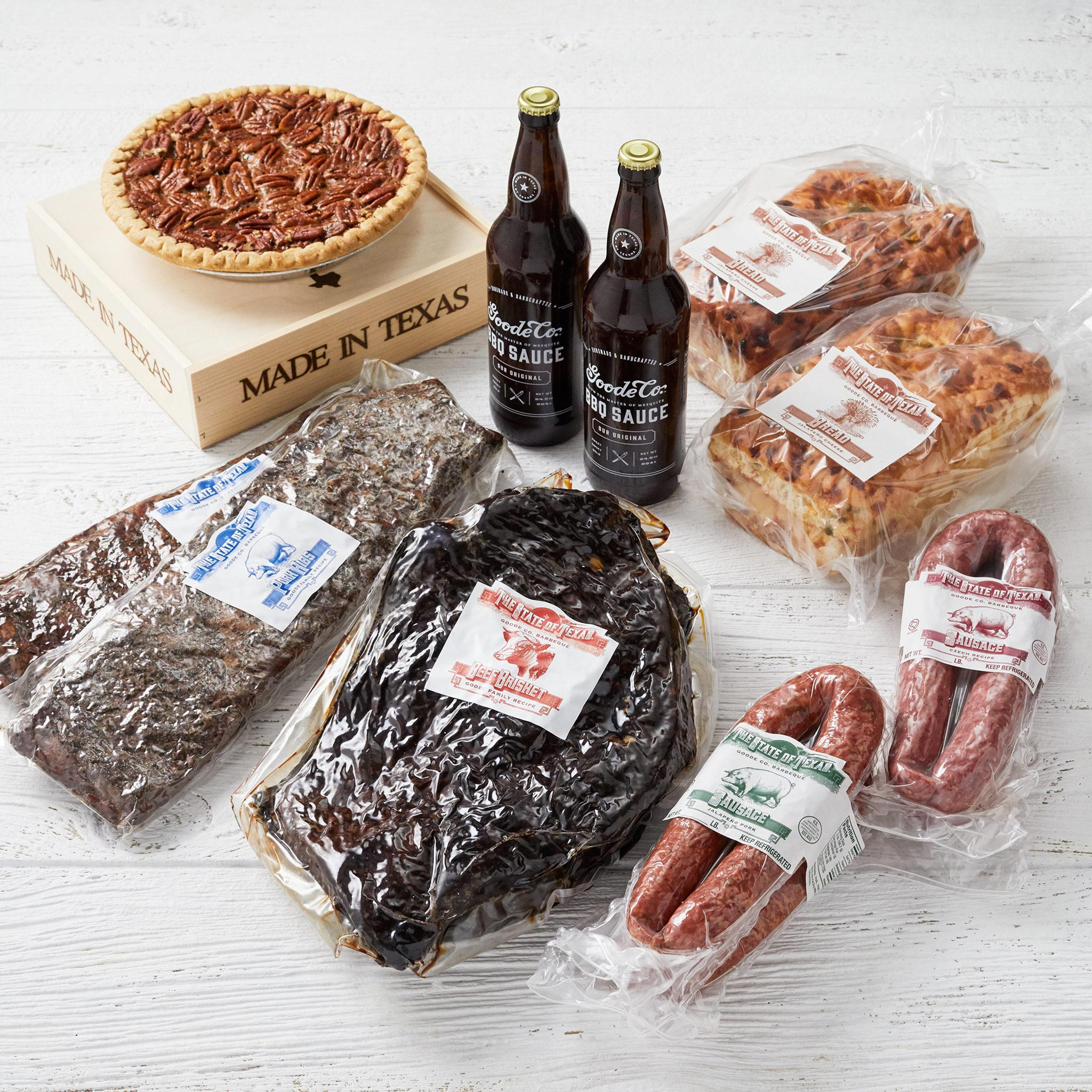 Shipping packaging of vacuum-sealed brisket, 2 slabs of ribs, 4 links of Texas sausage, 2 BBQ sauce bottles, and 2 loaves of jalapeño cheese bread, and our Brazos Bottom Pecan Pie in a wooden gift box.
