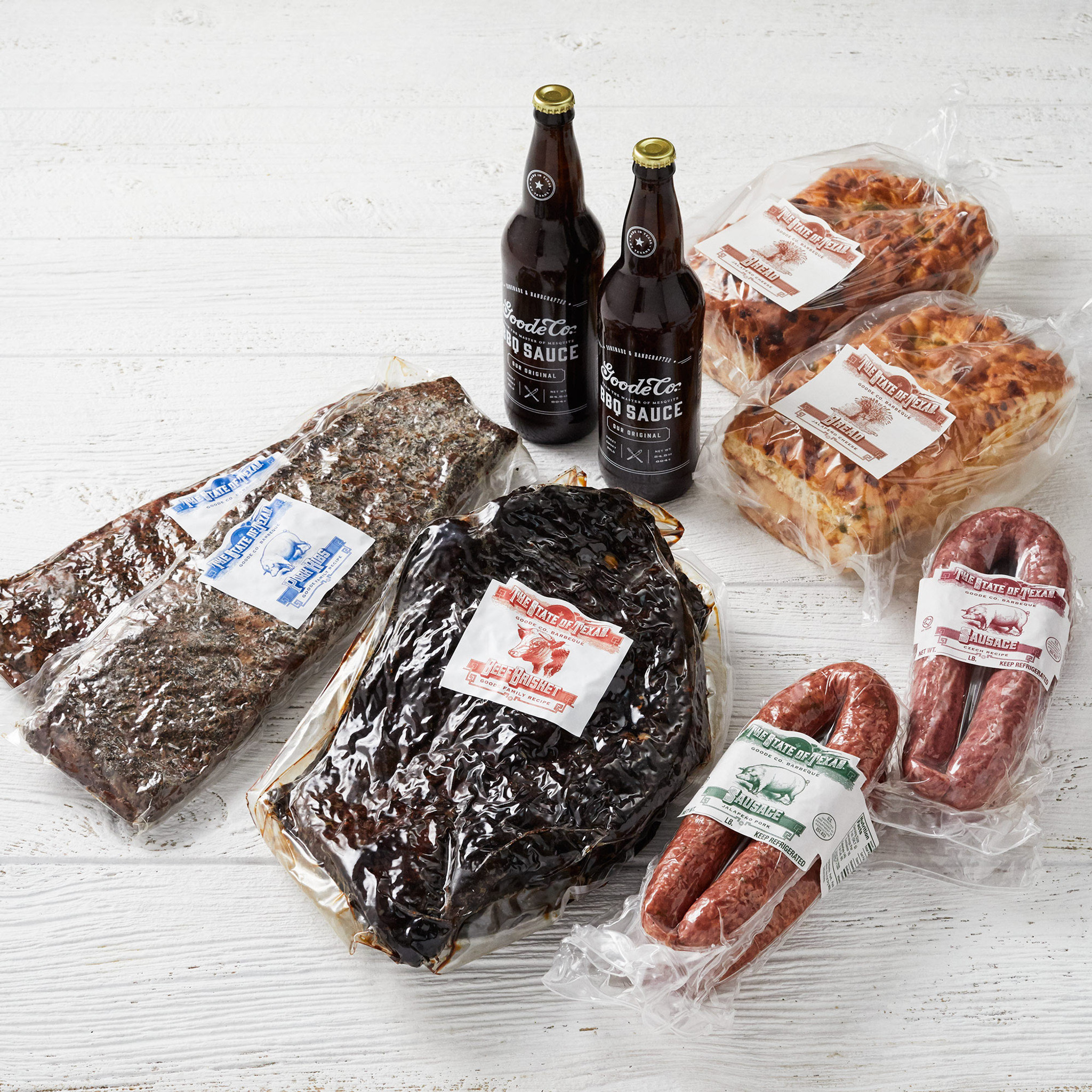 Shipping packaging for Goode Co's Davy Crockett meal bundle, delivered with vacuum-sealed smoked brisket, 2 pork ribs, 4 links of Texas sausages, 2 glass bottles of Goode's Original BBQ sauce, and 2 loaves of jalapeño cheese bread.