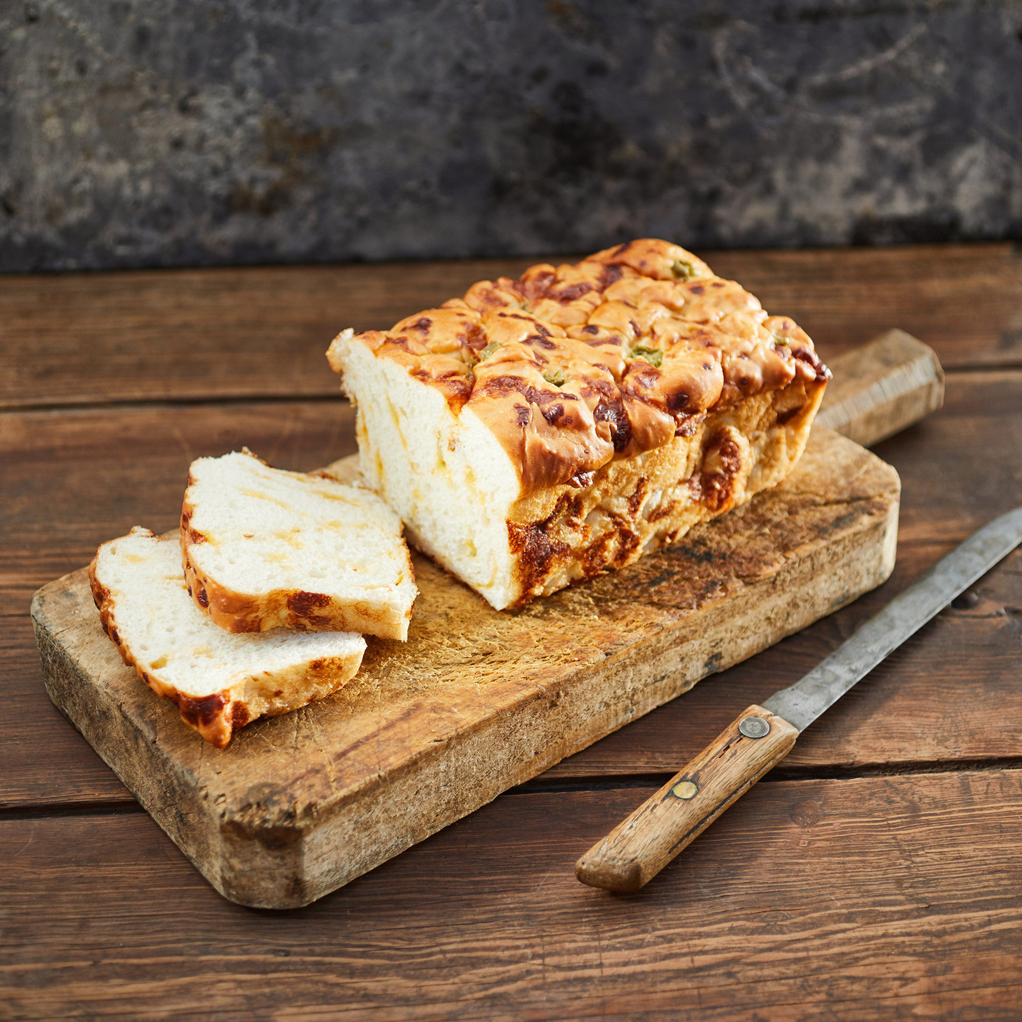 Goode Co's homemade Jalapeño Cheese Bread sliced and sitting on a wooden cutting board.