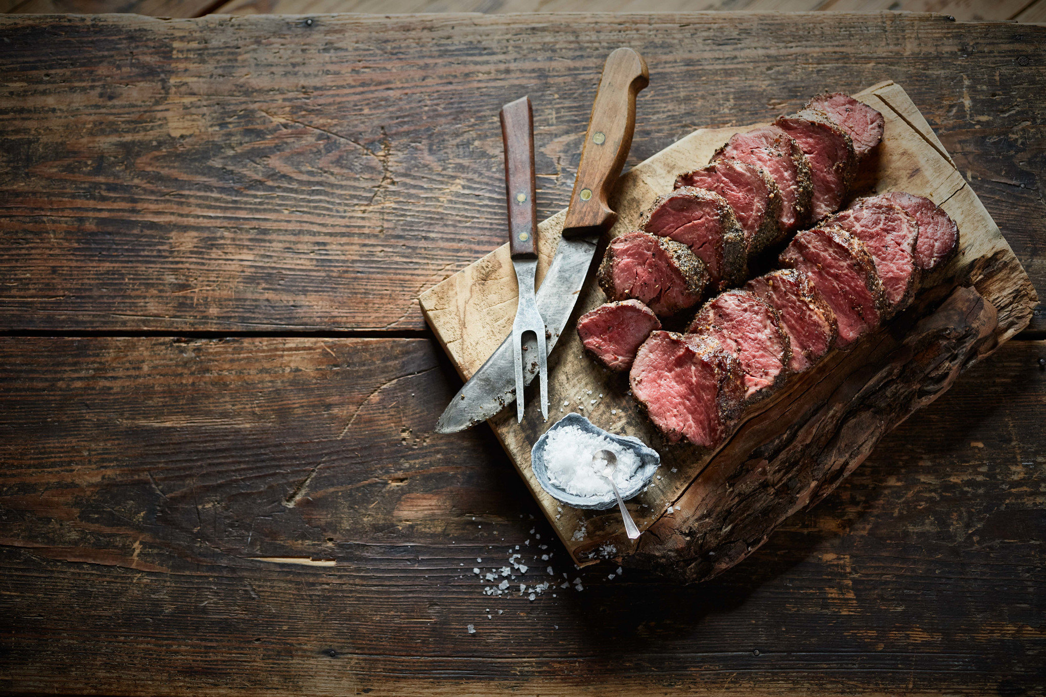 Smoked Beef Tenderloin that is sliced and laid neatly on a wooden cutting board next to a bowl of seasoning salt.