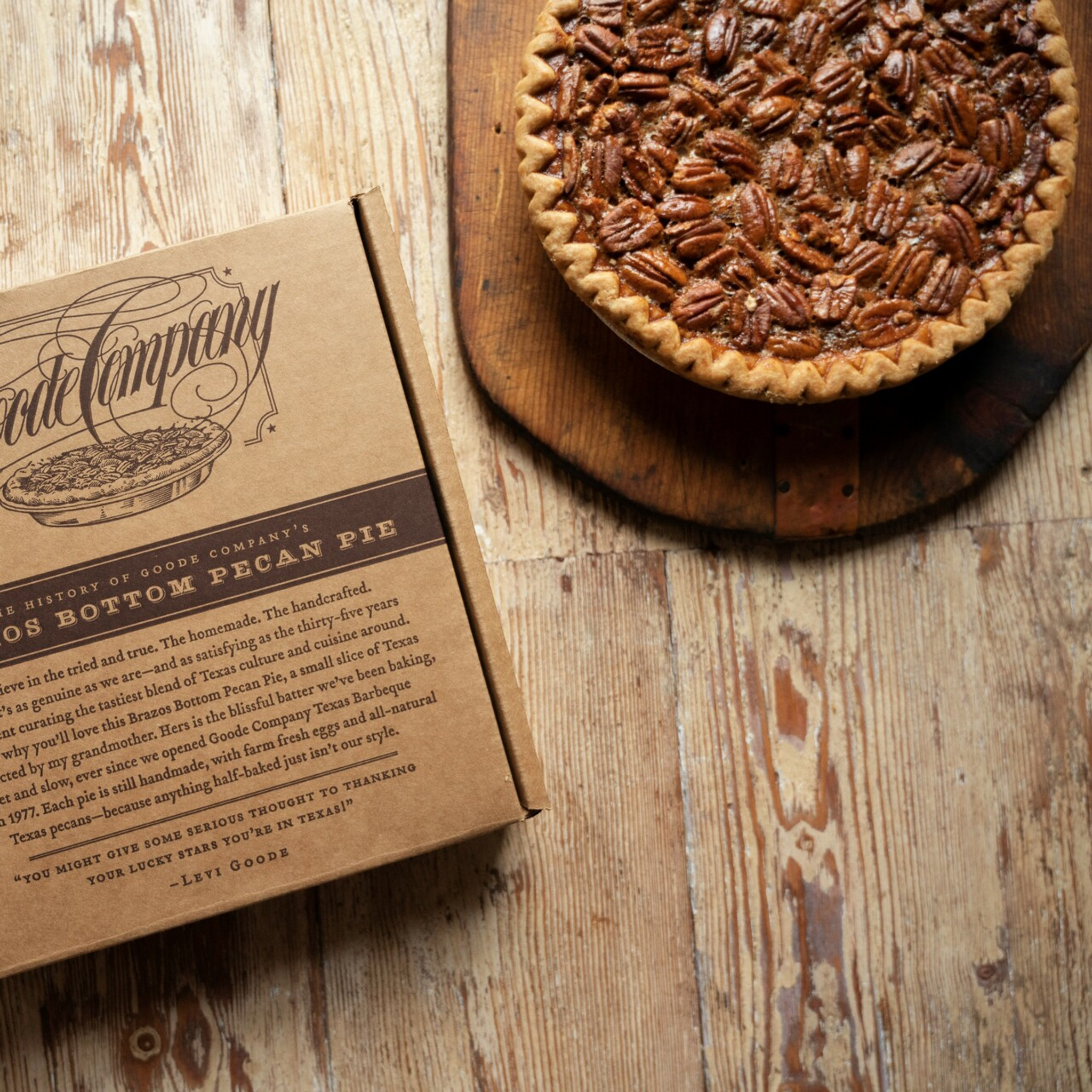 Brazos Bottom Pecan Pie shown on a wooden table next to the cardboard box that it is delivered in.