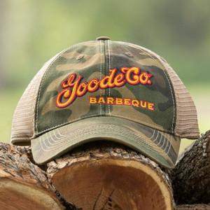 Goode Co's vintage camo trucker hat resting on Texas mesquite wood.