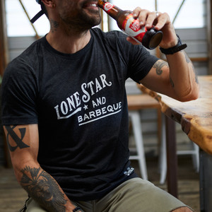 "Proud Texan wearing Goode Co's black cotton t-shirt that says ""Lone Star & BBQ"" in white font."