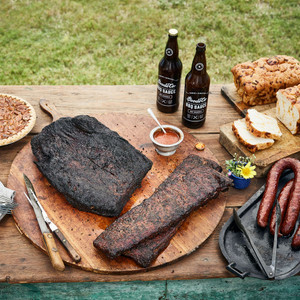 Goode Co's Pride of Sam Houston meal bundle, consisting of whole smoked brisket, 2 racks ribs, 4 links of Czech and jalapeño pork sausages, 2 24.5-ounce bottles of Goode's Original BBQ sauce, 2 loaves of jalapeño cheese bread, and our Brazos Bottom Pecan Pie.