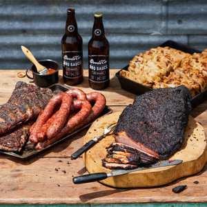 Goode Co's Davy Crockett meal bundle, consisting of whole smoked brisket, 2 racks ribs, 4 links of Czech and jalapeño pork sausages, bottle Goode's Original BBQ sauce, and 2 loaves of jalapeño cheese bread.