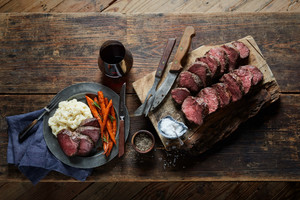 Sliced beef tenderloin, cooked medium rare, laid on a wooden cutting board next to a plate with a serving of beef and vegetables.