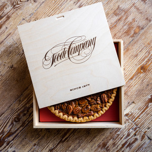 Pecan pie in a wooden box with the lid that shows the name Goode company written in script