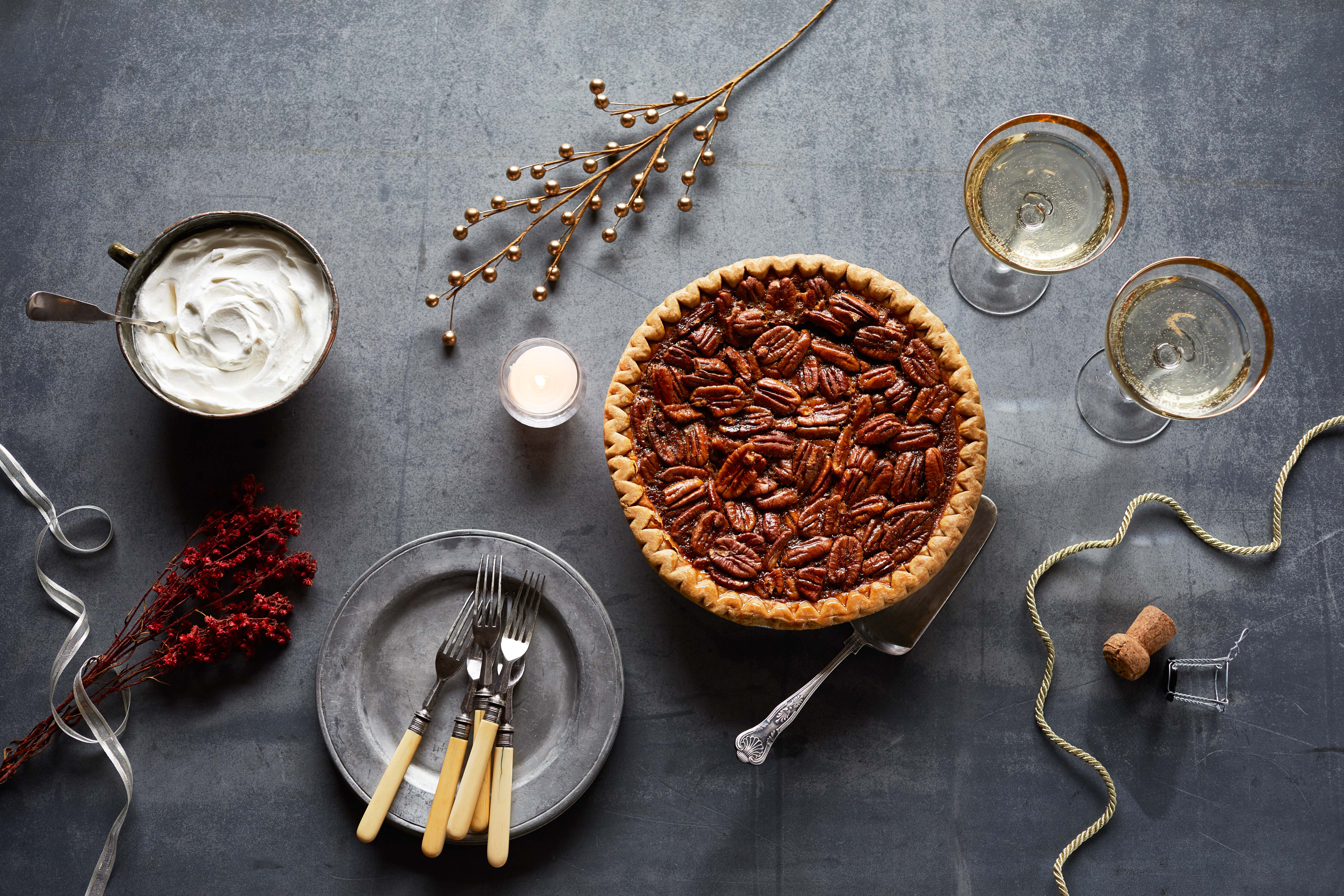 Table setting of whole pecan pies and plated pie slices