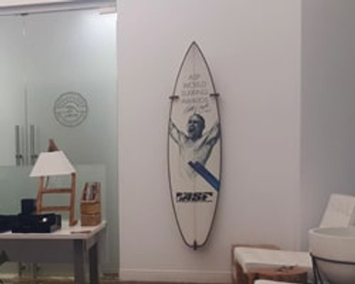 surfboard attached to wall with wooden clips