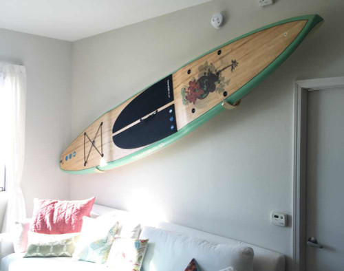 paddle board mounted to wall at an angle on paddle board rack