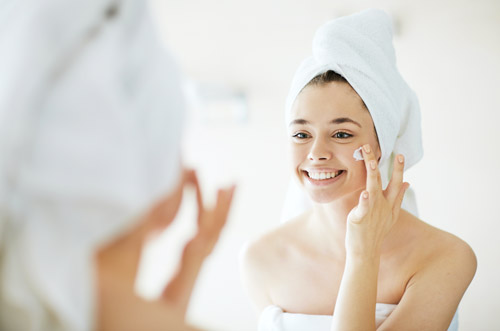 A smiling woman puts cream on her face
