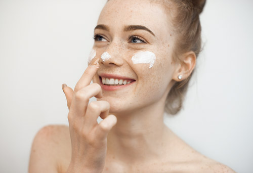 a woman putting cream on her nose